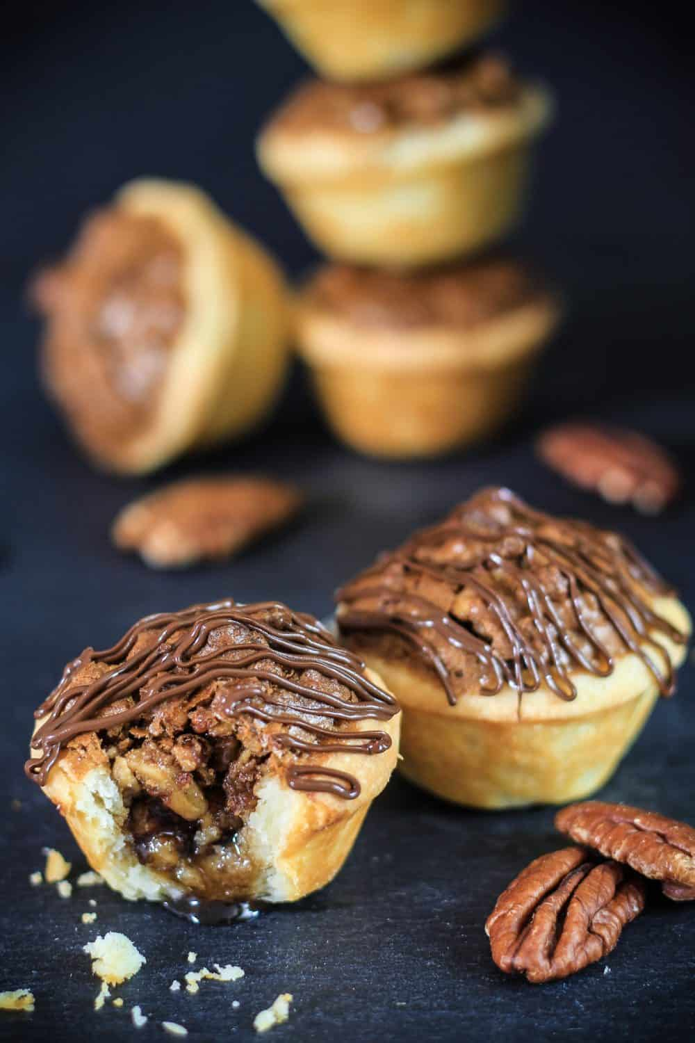 close up image of a bitten pecan tassies with melted chocolate drizzled on top