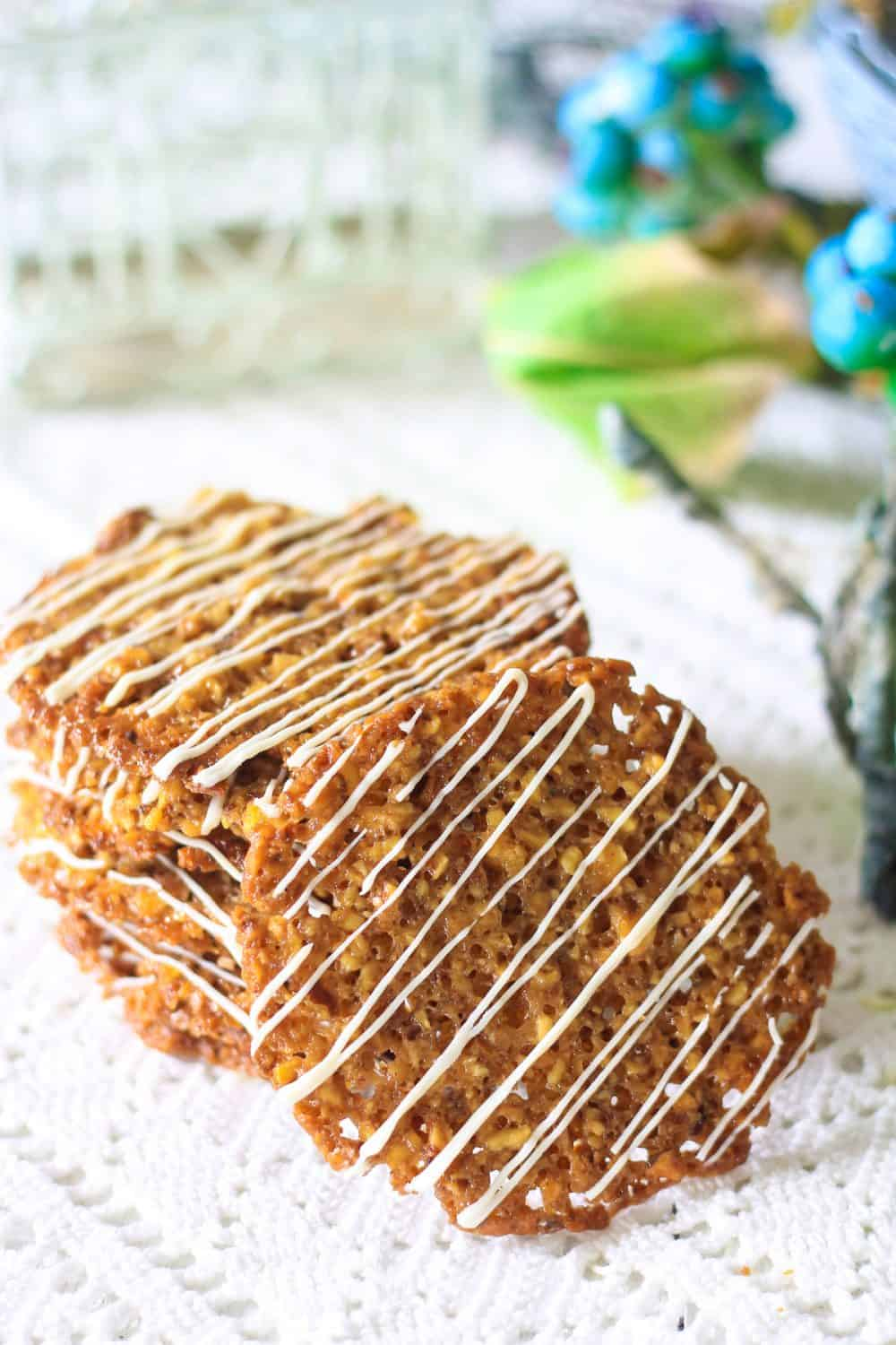 Photograph of a stack of florentine cookies with white chocolate drizzle laying on a lace tablecloth