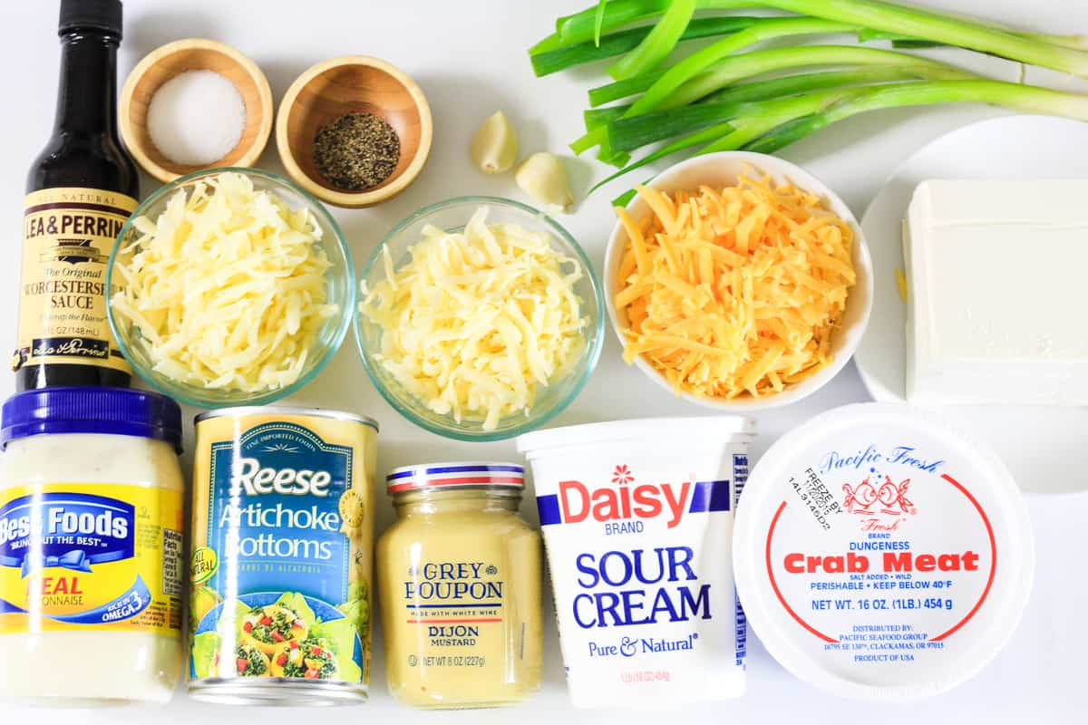 Ingredients for Crab Artichoke dip: Worcestershire sauce, fontina, cheddar, and monterey jack cheeses, green onions, garlic, bowls of salt and pepper, mayonnaise, artichoke bottoms, dijon mustard, sour cream, cream cheese, and crab meat, all on a white background.