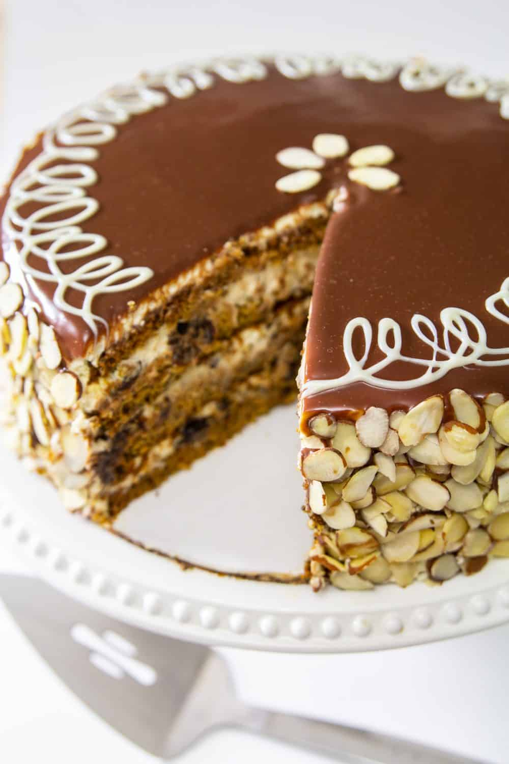Poppy Seed Honey Cake covered in chocolate ganache and sliced almonds, with one slice cut out on a white plate and white background.