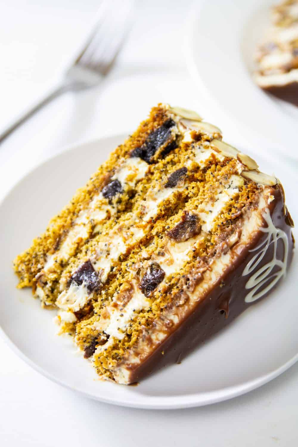 Close up of slice of Poppy Seed Honey Cake on a white plate with a fork and another slice on a white background