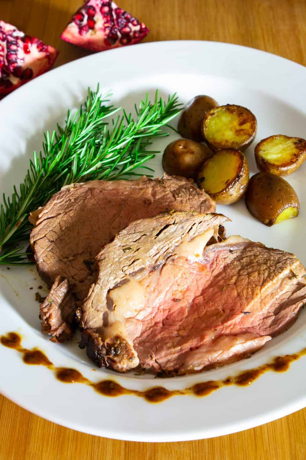 Slide of prime rib roast with potatoes and a spring of rosemary on a white plate, pomegranate slices in the background