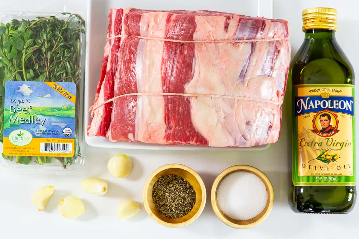 Ingredients for prime rib roast: fresh herb mix, prime rib, bottle of olive oil, gloves of garlic, bowls with salt and pepper on a white background