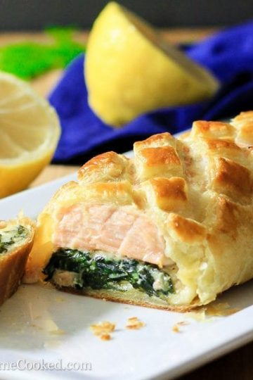 Sliced salmon Wellington in a white dish with sliced lemon around it