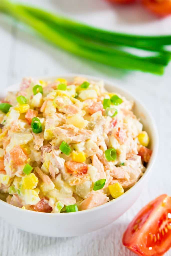 potato salad with baked salmon in a white bowl with a slice of tomato and a bunch of green onion next to it.