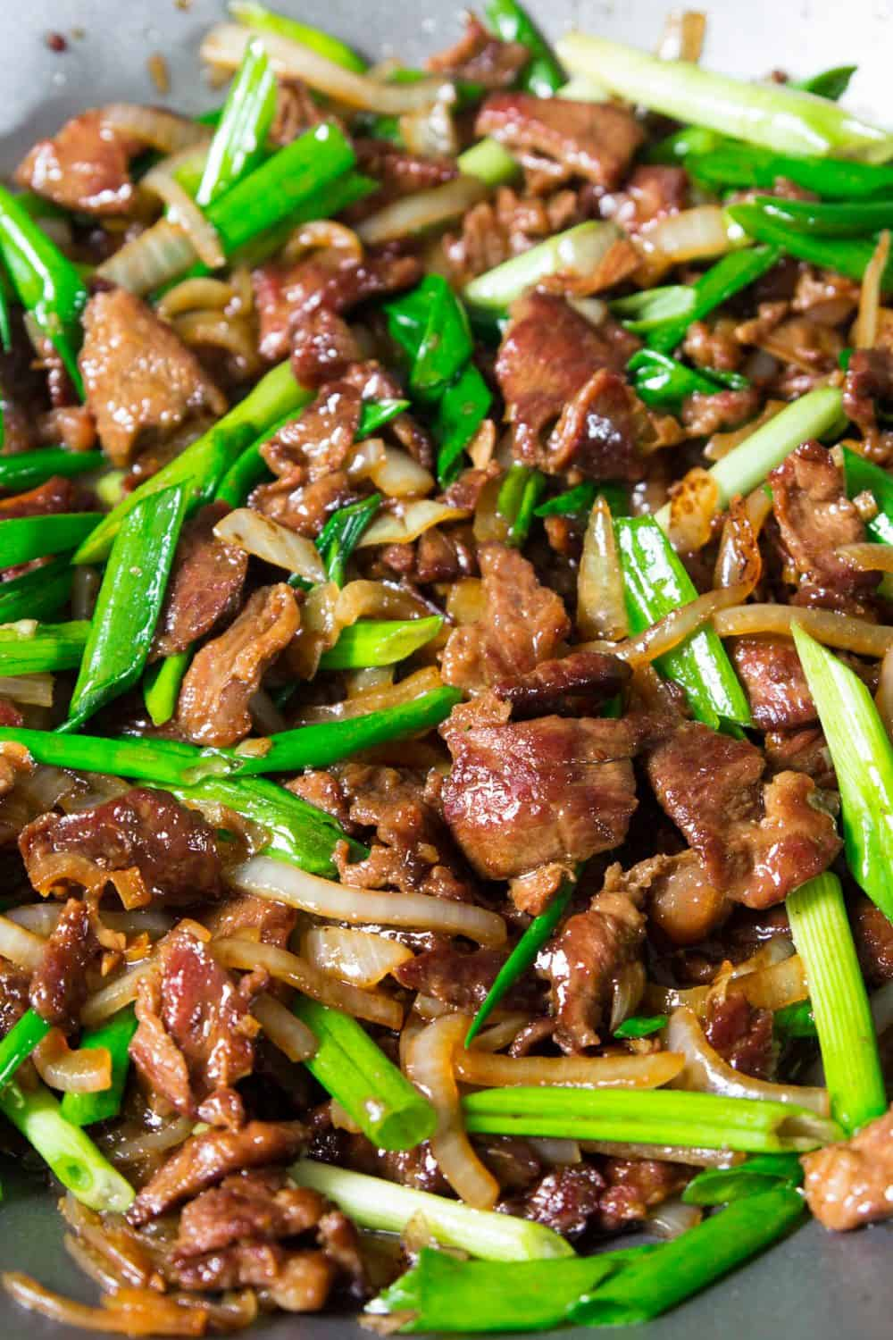 cooked beef and green onion in a wok