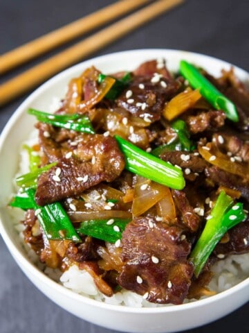 cooked Mongolian beef and green onion in a white bowl with white rice and chopsticks beside it.