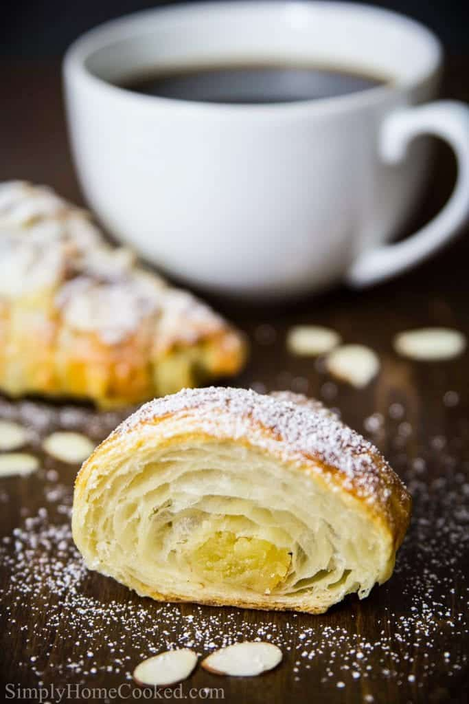 sliced almond croissant with a cup of coffee beside it
