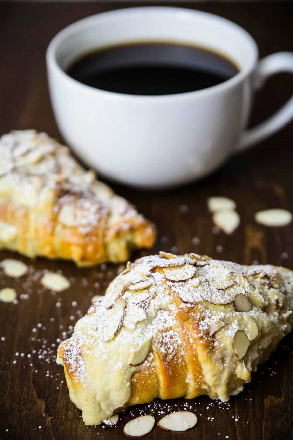 almond croissant with a cup of coffee beside it