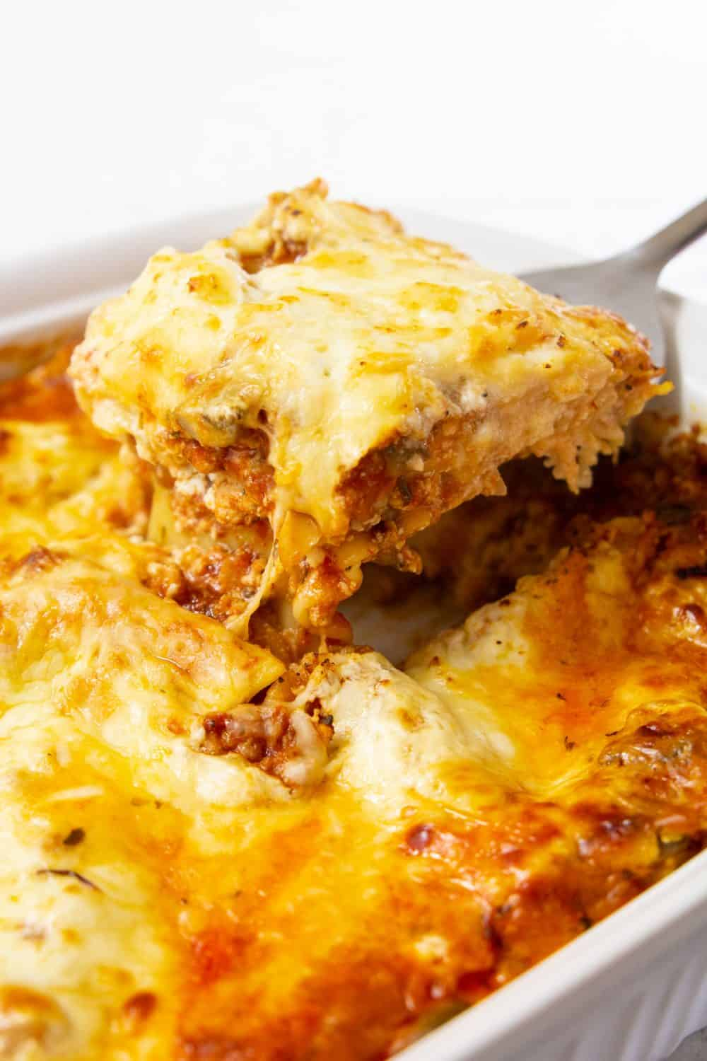Close up image of cooked chicken lasagna recipe with one portion being scooped out with a spatula showing the melted cheese and layers of pasta and meat sauce