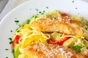 pan fried chicken tenders, pasta, and sautéed peppers in a white plate