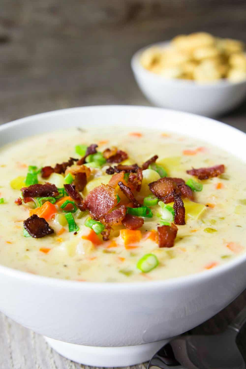 A large white bowl on a wooden table full of clam chowder soup that has been topped with bacon crumbles and diced green onions