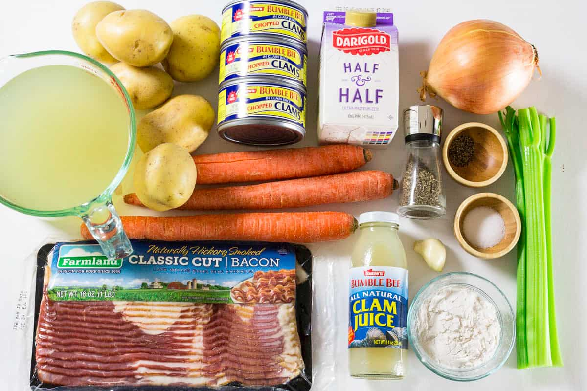 Ingredients for clam chowder soup laying on a flat white surface and photographed from above