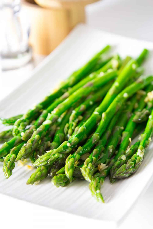 garlic asparagus on a white plate