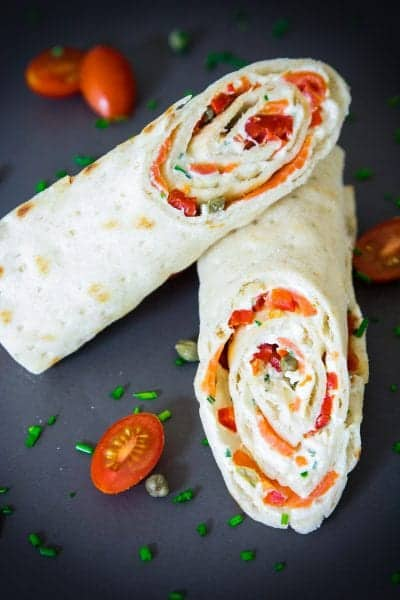 sliced smoked salmon wrap with cherry tomatoes and chopped chives next to it