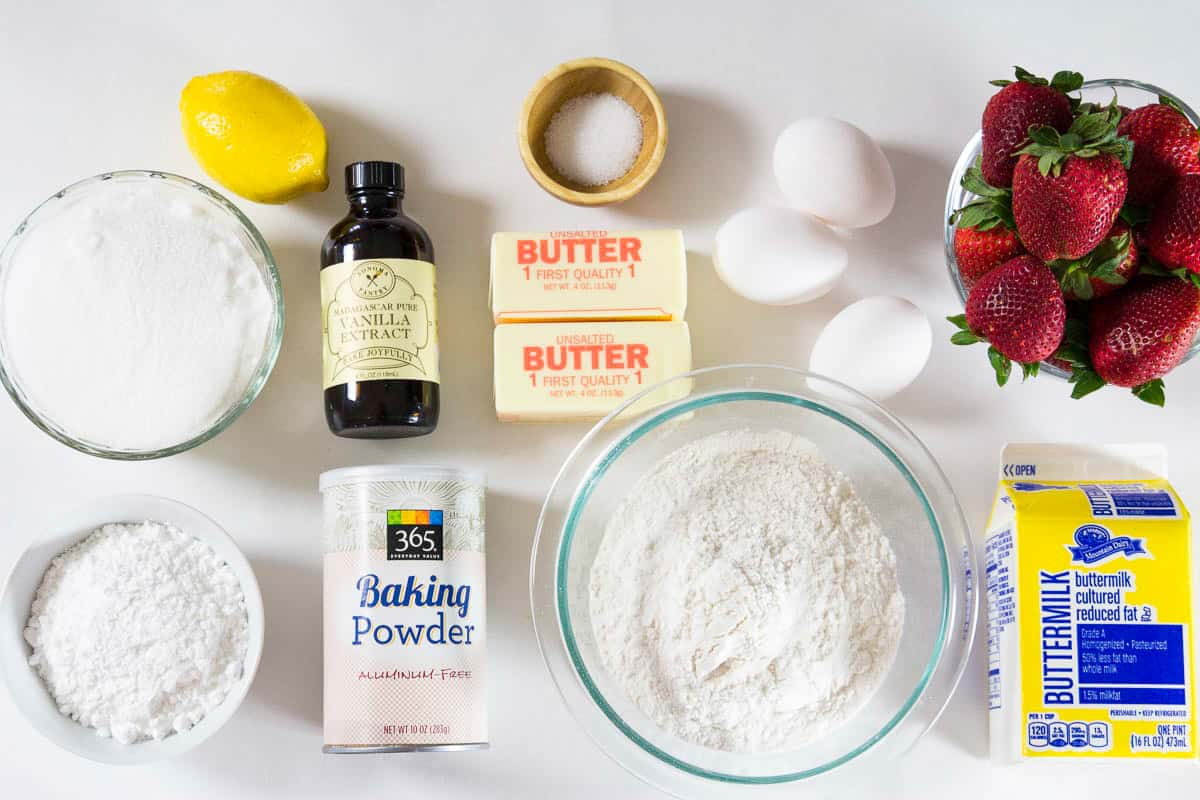 Ingredients for strawberry bundt cake displayed on flat white surface