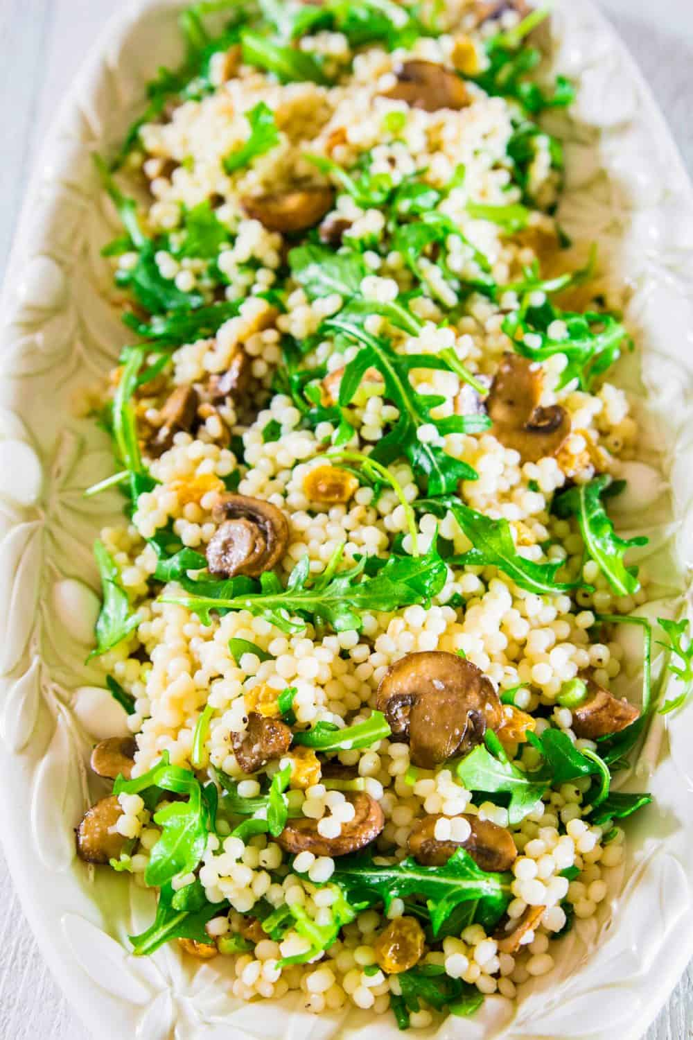 a close up image of a couscous salad mixed with baby arugula, cooked mushrooms, and golden raisins