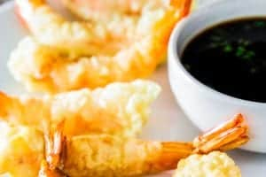 Fried tempura shrimp on a plate with soy sauce next to it