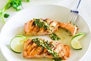 2 salmon fillets on a plate with cilantro dressing on top. some cilantro and slices of limes on the side