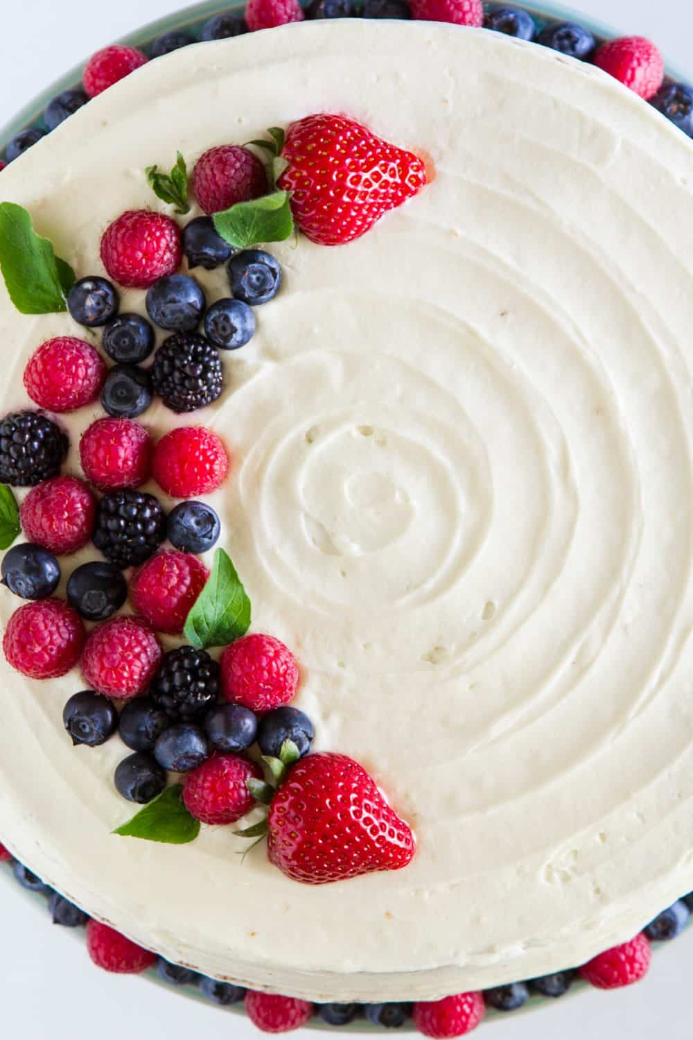 white Chantilly cake with berries on top