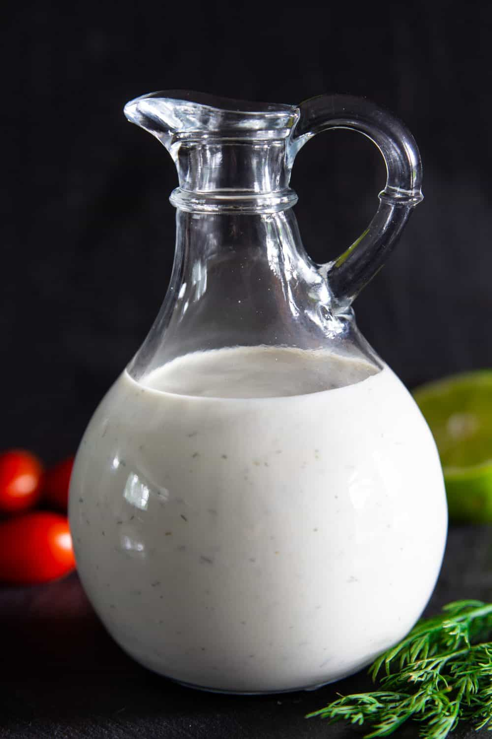 Dressing bottle filled with Buttermilk Ranch Dressing and some tomatoes, lime, and dill in the background.