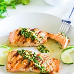 grilled cilantro lime salmon on a white plate with sliced lime beside it.