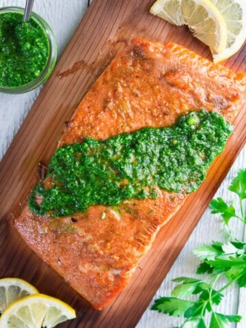 grilled salmon on cedar plank with chimichuri sauce on top and sliced lemons beside it.