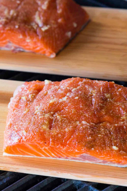 seasoned salmon fillet on a cedar plank on a grill