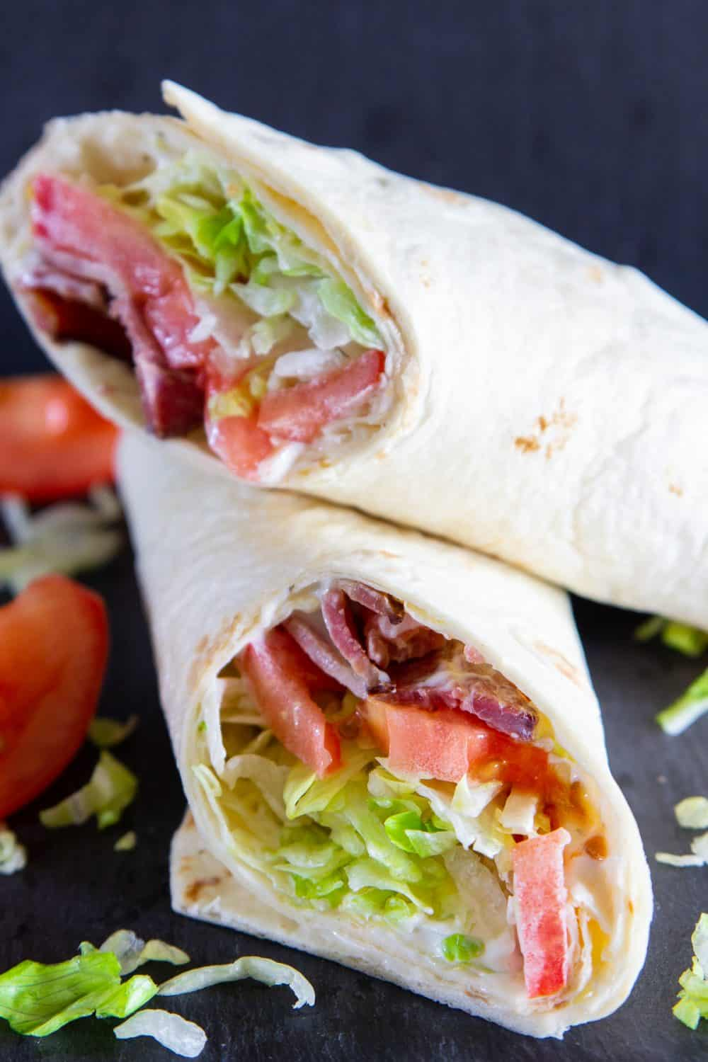 Close up of BLT wrap cut in half and stacked with shredded lettuce and sliced tomatoes on a dark background.