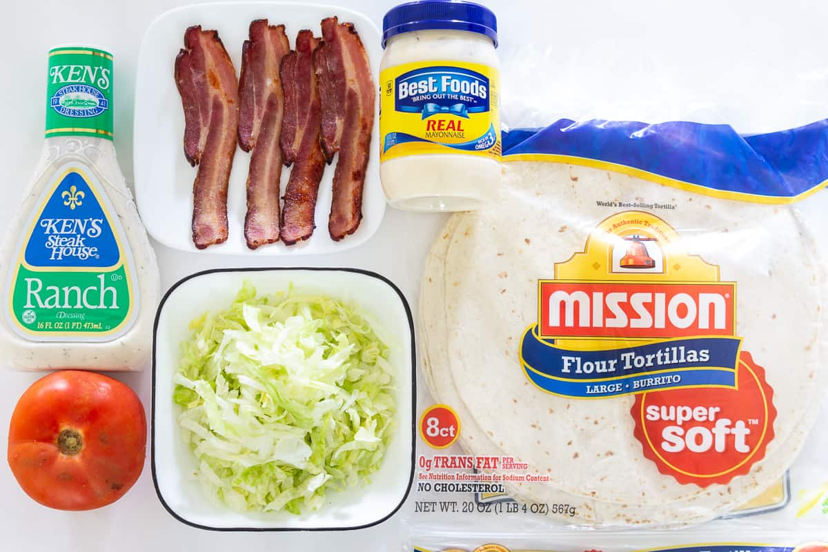 Image of ingredients for BLT wrap: mayonnaise, ranch, bacon slices, shredded lettuce, tomato, and flour tortillas, all on a white background.
