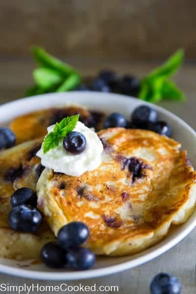 Blueberry ricotta pancakes with whipped cream and blueberries on top