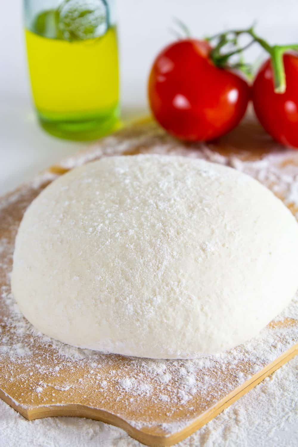 a close up image of a homemade pizza dough on a wooden cutting board with tomatoes, and olive oil in the background
