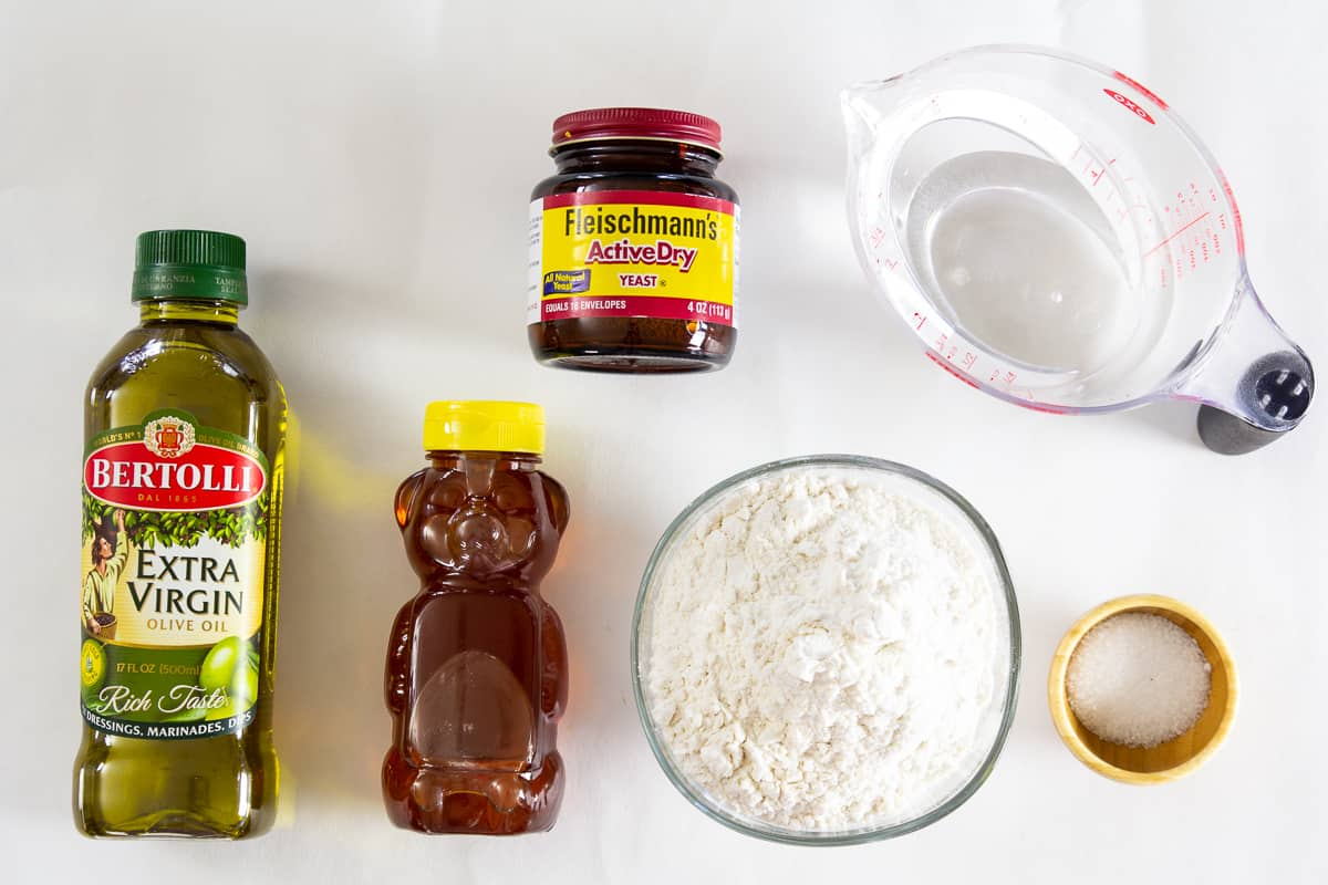 an overhead image of ingredients for pizza dough on a white background
