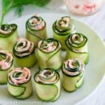 smoked salmon spread rolled inside of thinly sliced cucumbers on a white plate
