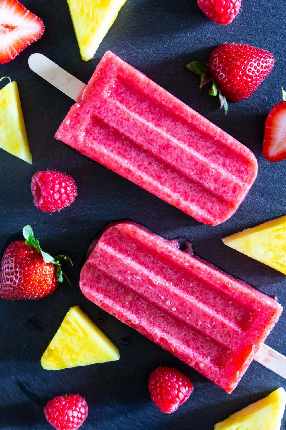Strawberry pineapple fruit popsicles laying on a black surface with chunks of pineapple and fresh berries laying around them.