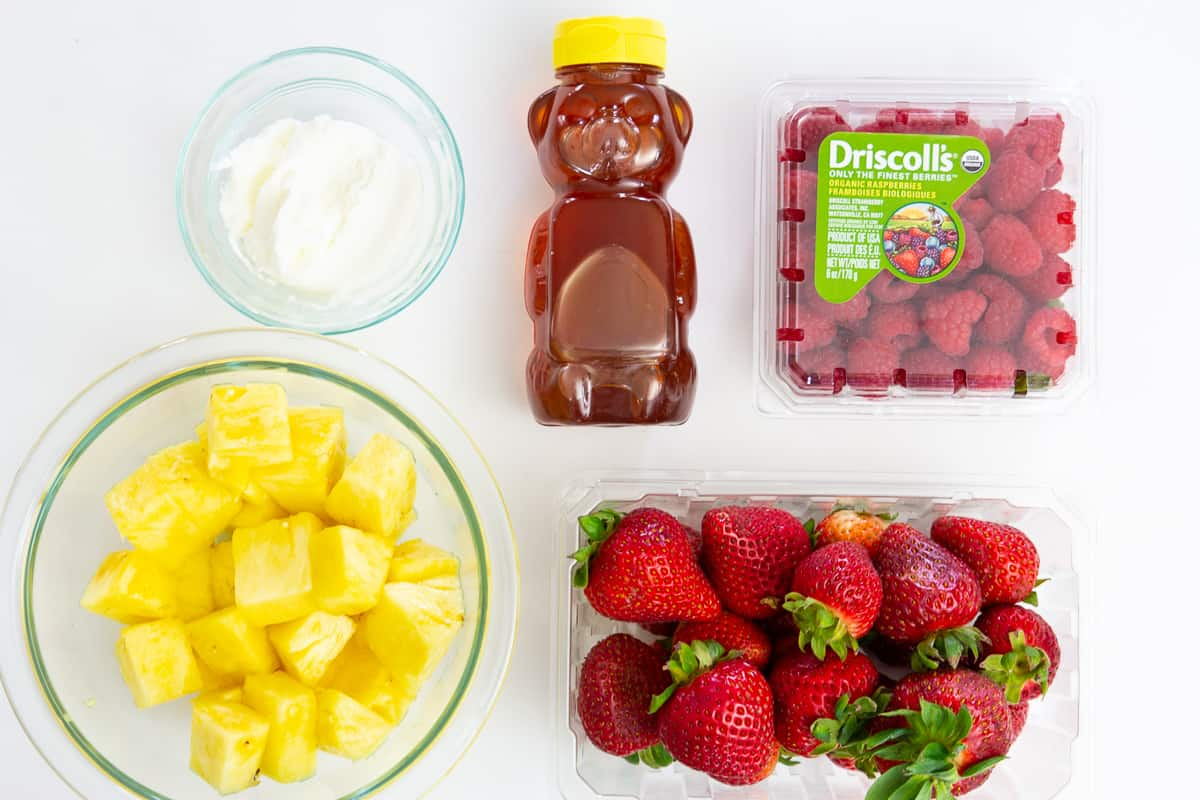 ingredients for fruit popsicles laying on a flat white surface and photographed from overhead