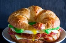 Croissant breakfast sandwich with bacon, avocado, cheese, and eggs