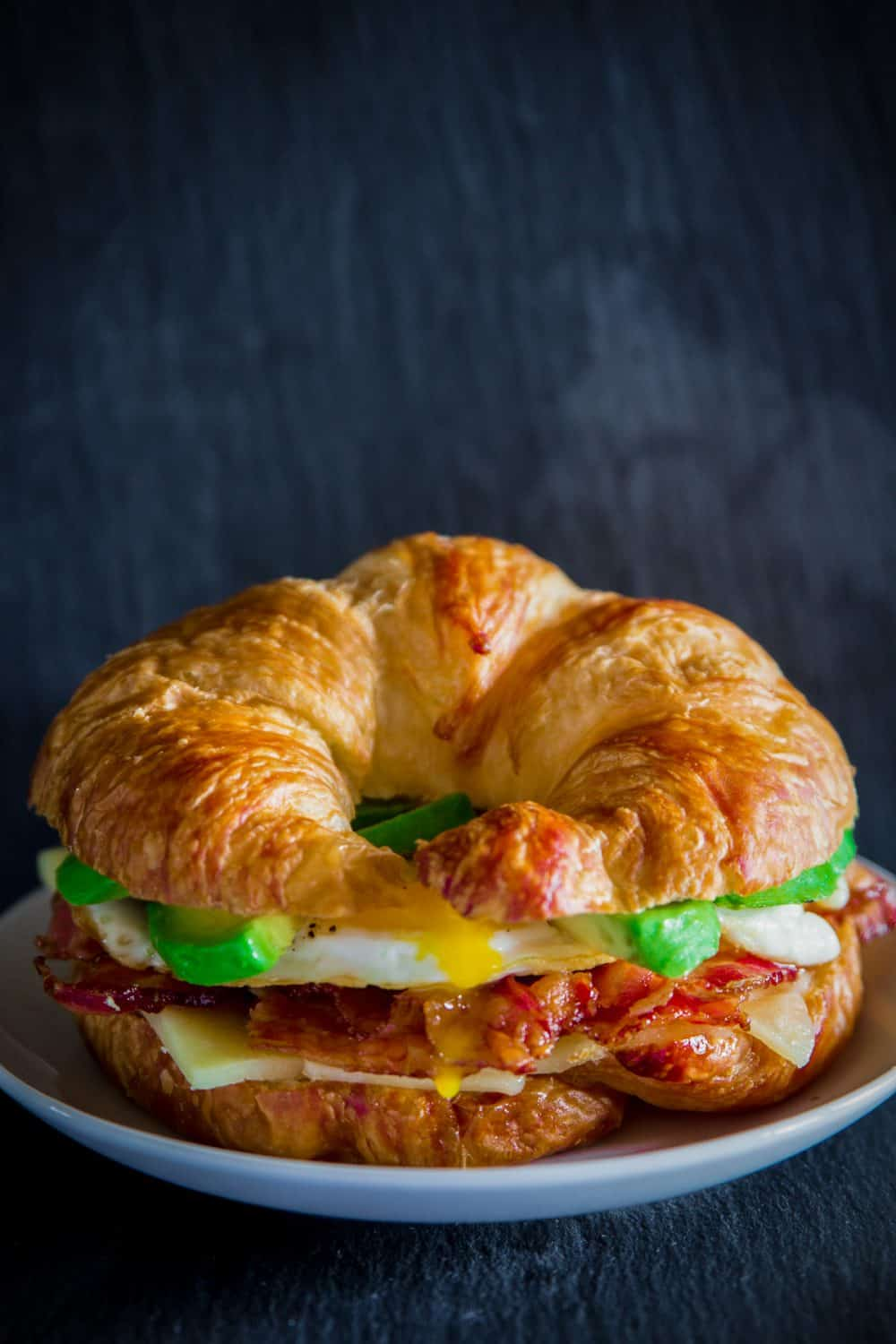 croissant sandwich with egg, bacon, cheese, and avocado on a white plate