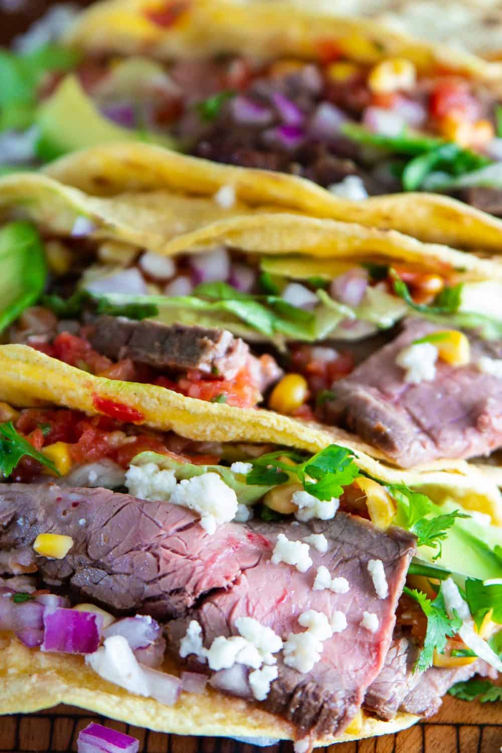 Up close picture of steak taco recipe featuring grilled flank steak, corn tortillas, cilantro, salsa, and cheese