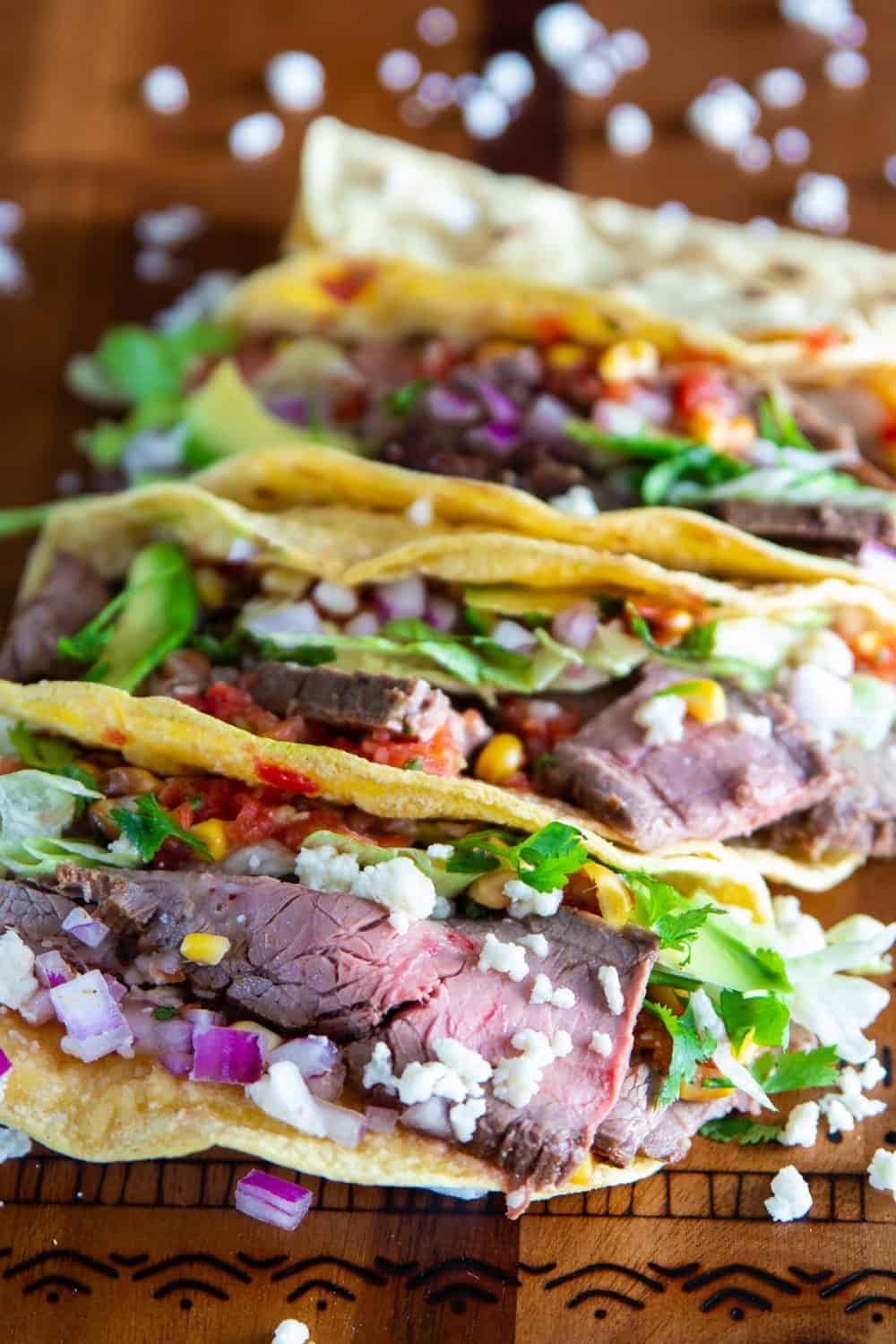 Overhead picture of steak taco recipe featuring flank steak in corn tortillas topped with fresh cheese, red onions, corn salsa, and cilantro sitting on a wooden surface
