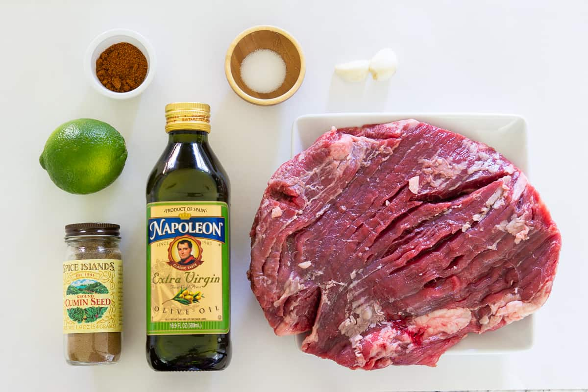 Ingredients for steak taco recipe laying flat on a white surface