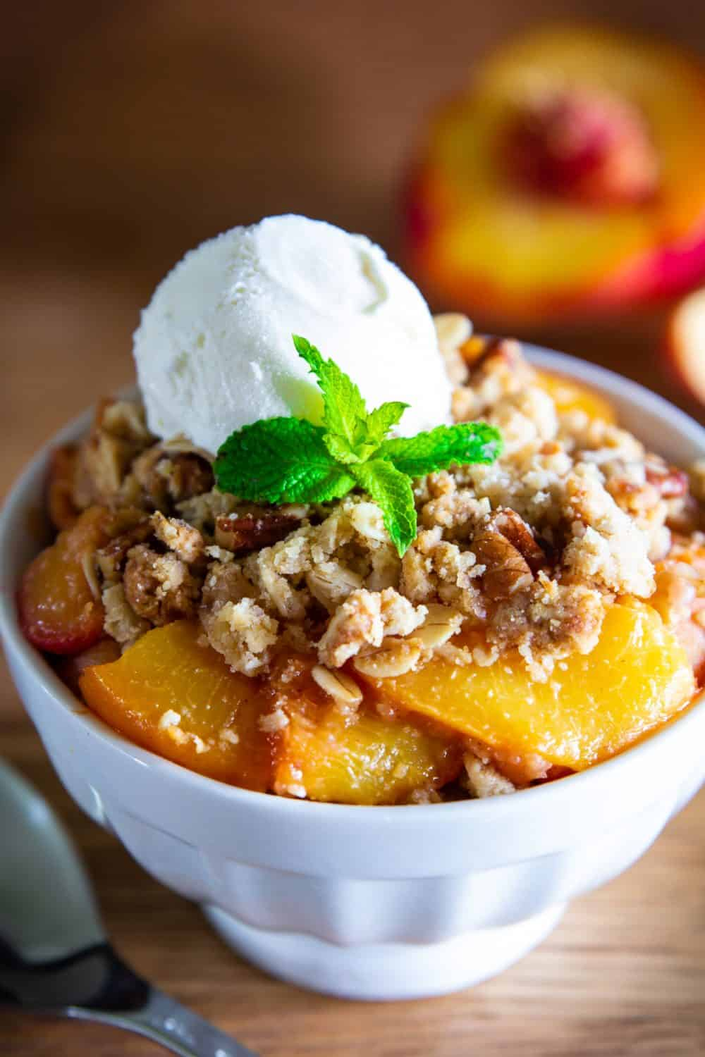 close up image of homemade peach crisp with crumb topping and vanilla ice cream on top with a garnish of mint