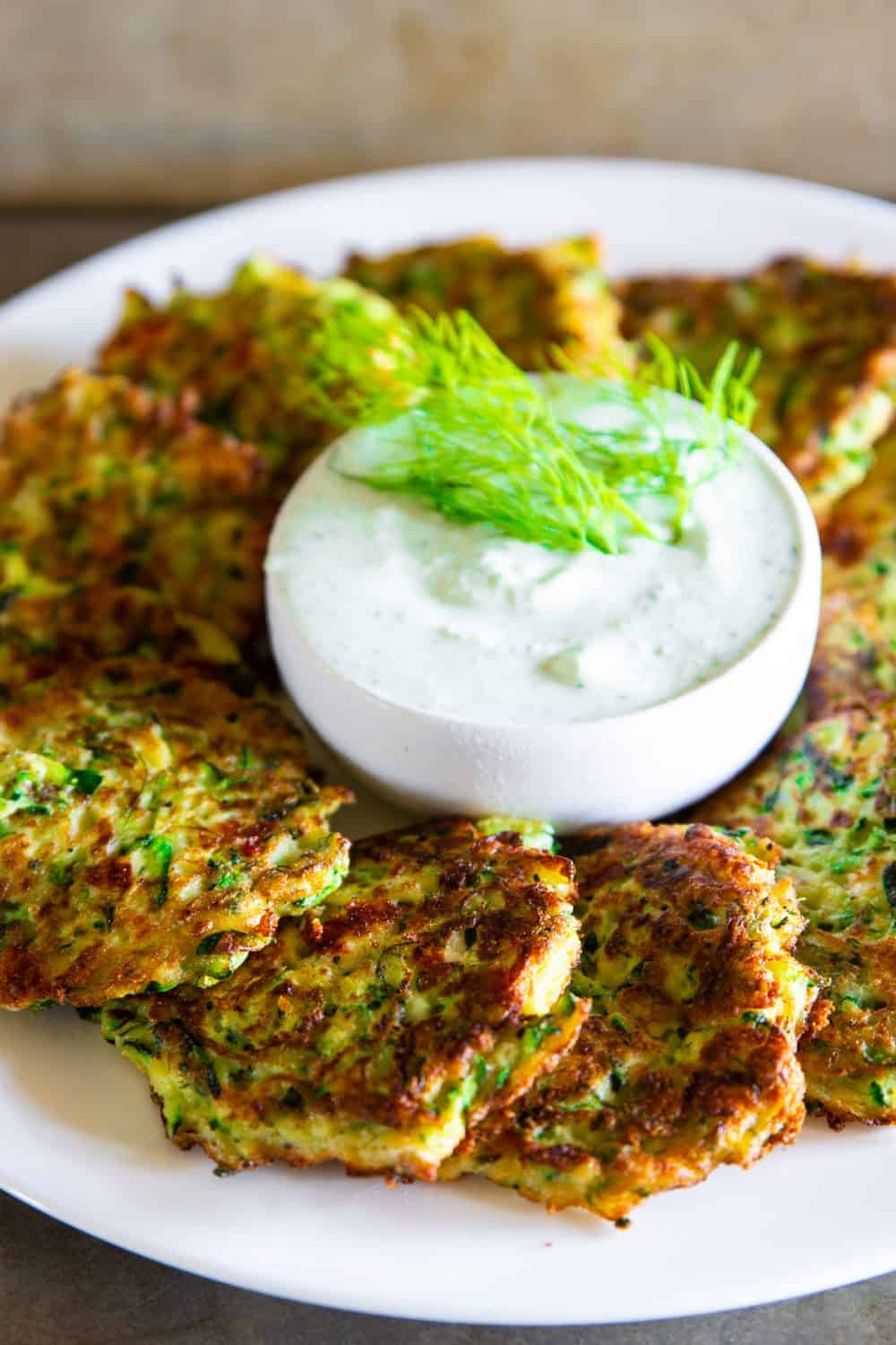 greek zucchini fritters laid next to each other on a round white plate with a small bowl of greek yogurt sauce and fresh dill on top