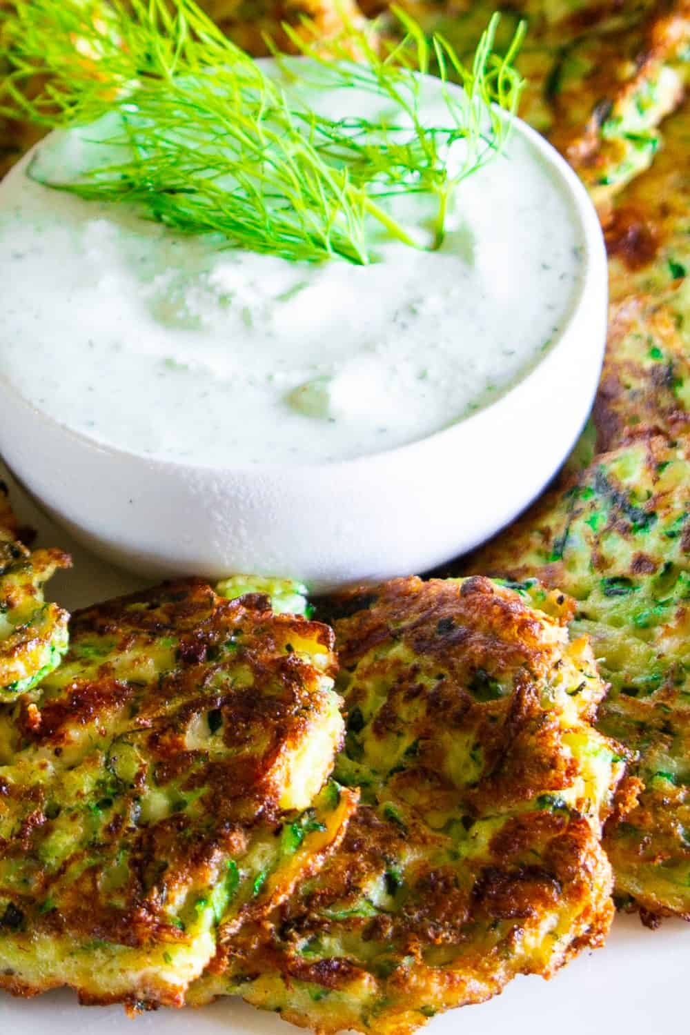 a close up photo of zucchini fritters a greek yogurt sauce with fresh dill on top