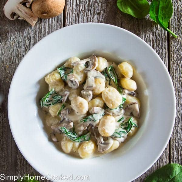 mushroom gnocchi with spinach in a white bowl