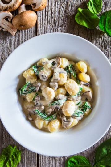 creamy mushroom gnocchi with spinach in a white bowl with fresh spinach and raw mushrooms beside it