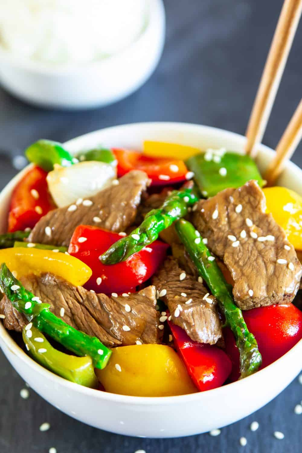 Close up of Pepper Steak stir fry with chopsticks in a white bowl