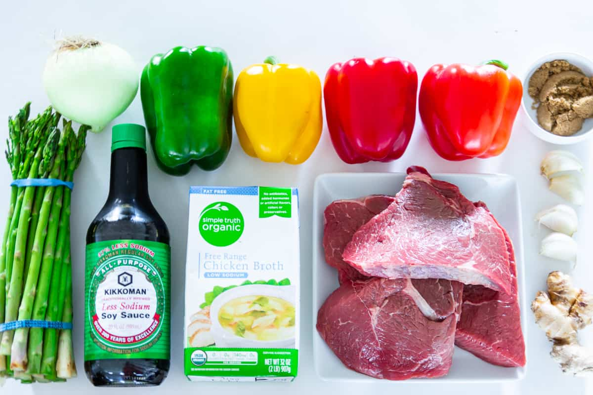 Ingredients for pepper steak: bottle of soy sauce, red, yellow, and green peppers, onion, garlic, ginger, asparagus, chicken broth, brown sugar, and sirloin steak, all on a white background.