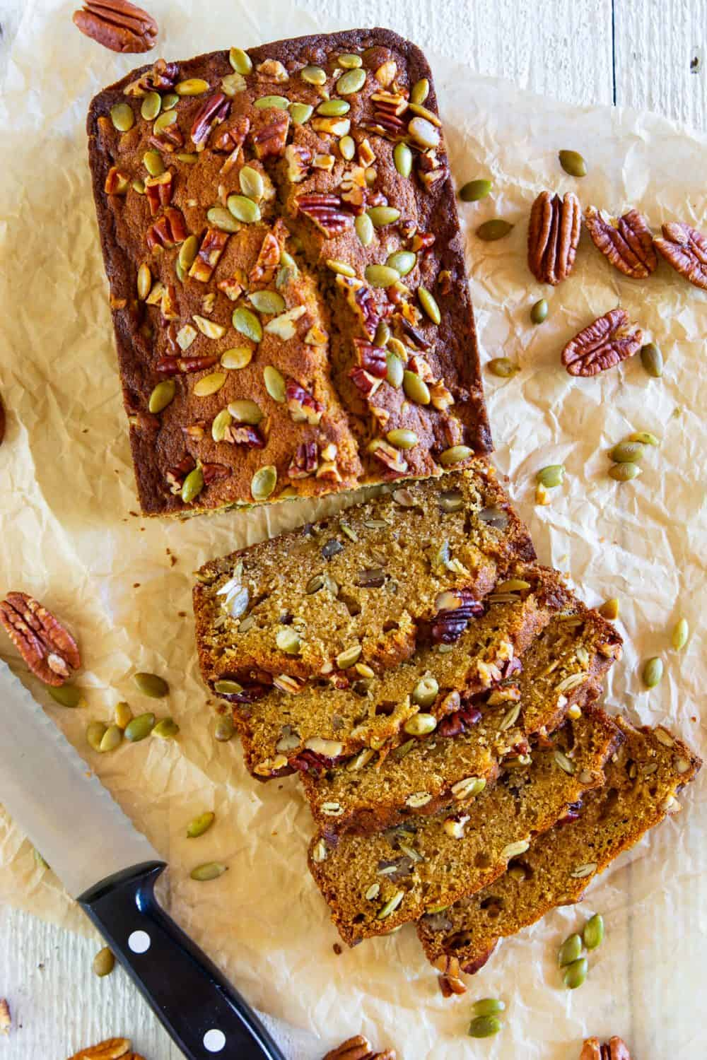 an overhead image of a baked pumpkin bread loaf with pecans and pumpkin seeds sprinkled on top