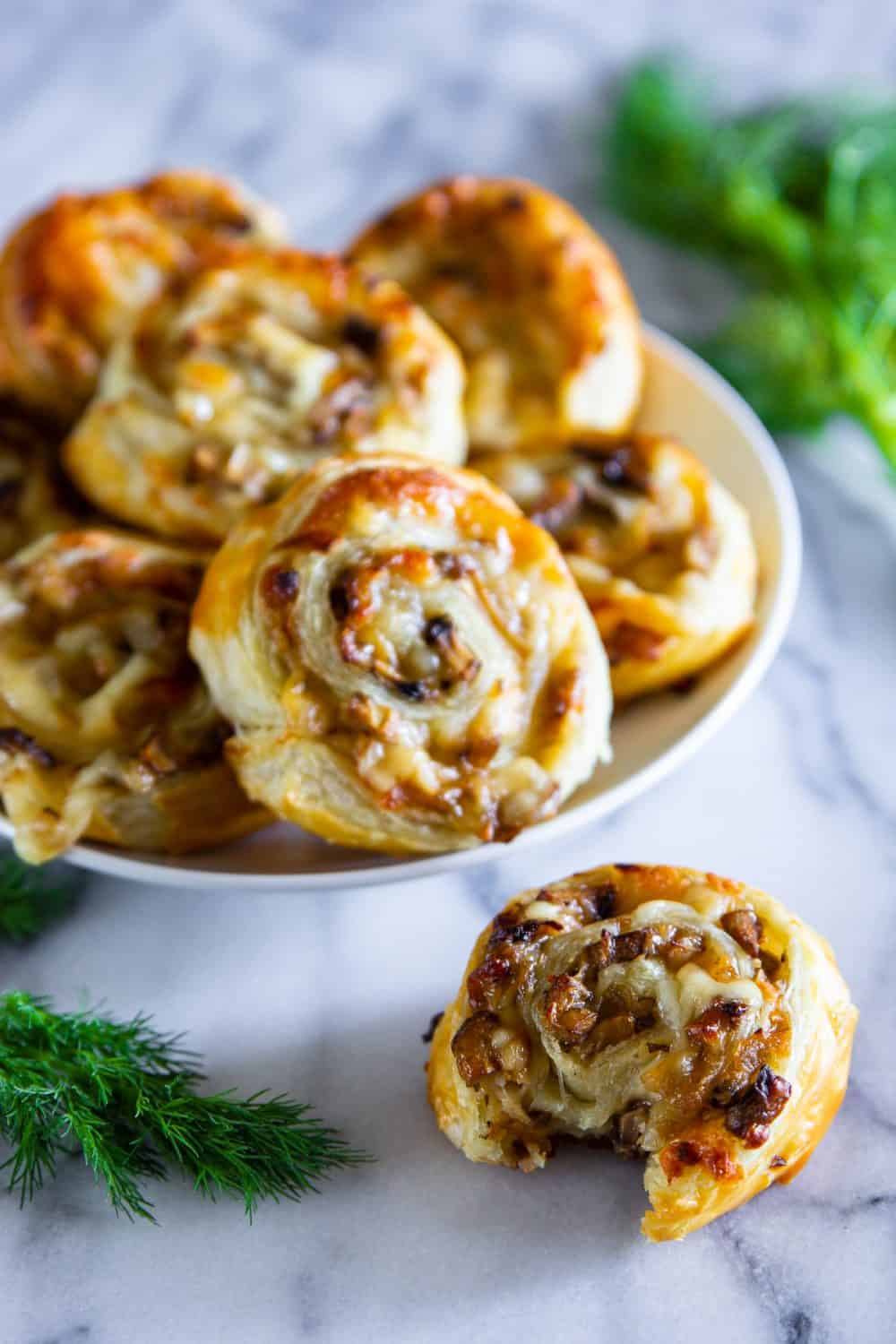 Close up display of mushroom and cheese puff pastry pinwheels on a white display stand and marble counter top alongside fresh dill.
